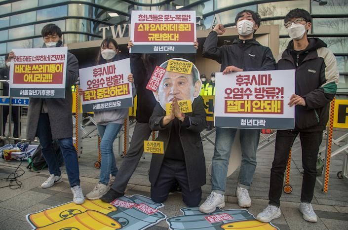 SEOUL, SOUTH KOREA - 2021/04/13: An activist wearing a cut out depicting Japanese Prime Minister Yoshihide Suga, while colleagues holding placards expressing their opinion during the demonstration. South Korean activists protest against the Japanese government's decision to discharge radioactive water from Fukushima Daiichi Nuclear Power Plant in Japan, in front of the Japanese Embassy in Seoul. (Photo by Jaewon Lee/SOPA Images/LightRocket via Getty Images)