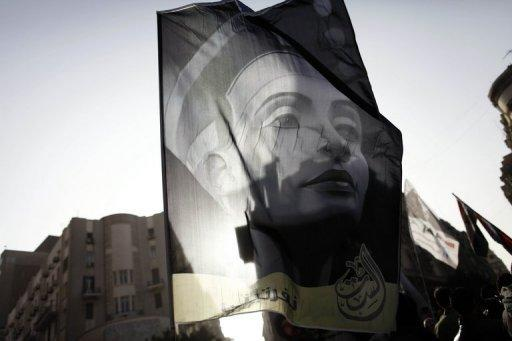 """Egyptians wave a flag bearing the portrait of Queen Nefertiti as they march in downtown Cairo to mark International Women's Day on March 8, 2013. """"Women are the slaves of this age. This is unacceptable and particularly in our region,"""" Mervat Tallawy, who headed the Egyptian delegation at a United Nations said"""