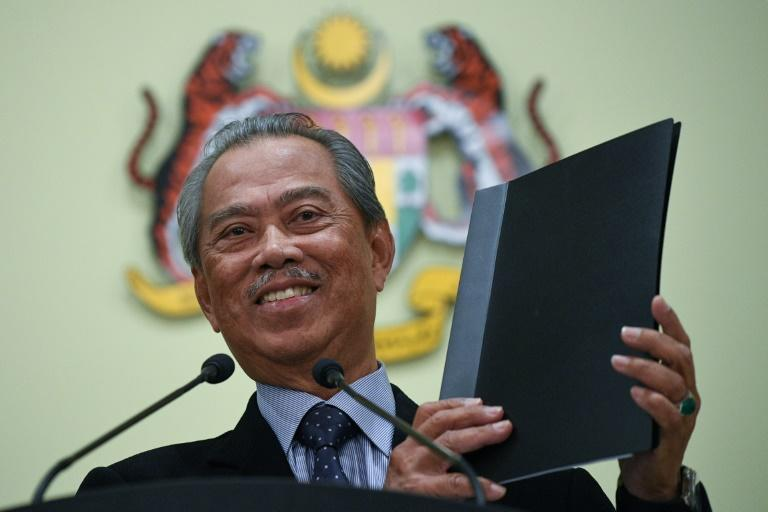Malaysia's Prime Minister Muhyiddin Yassin holds a folder after unveiling his new cabinet