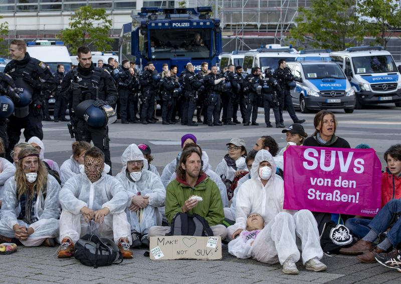 Activists block the main entrance of the fairground in Frankfurt, Germany, Sunday, Sept. 15, 2019. They protest against the government's transport policy on occasion of the IIA Auto Show taking place. The poster reads: 'SUV's out of the streets'. (AP Photo/Michael Probst)