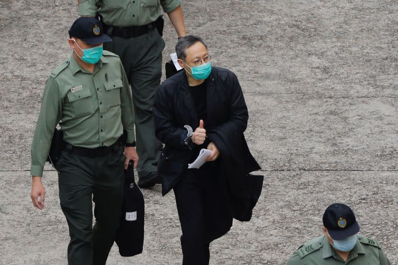 Pro-democracy activist Benny Tai flashes thumbs up as he walks to a prison van to head to court, over the national security law charge, in the early morning, in Hong Kong