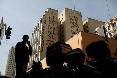 "A man stands in front of a building tagged by ""pichadores"", graffiti artists who tag buildings and landmarks with angular, runic fonts, with their personal signatures, called ""pichacao"", on a street in Sao Paulo, Brazil, April 20, 2017. REUTERS/Nacho Doce"
