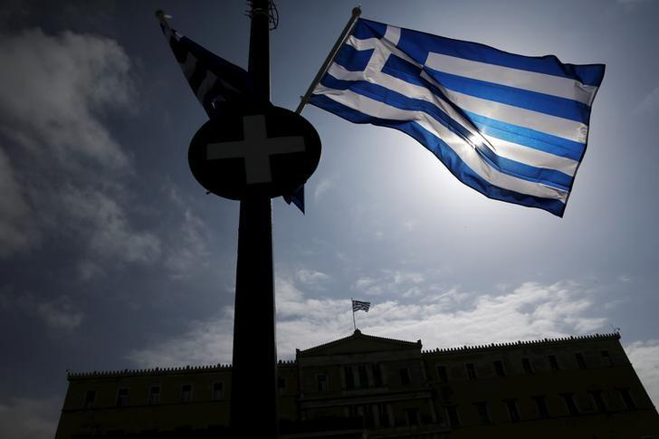 A Greek national flag flutters as the parliament building is seen in the background in Athens