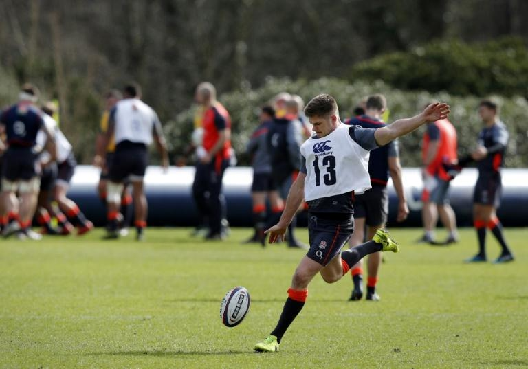 England's centre Owen Farrell prepares to kick the ball during a team training session west of London