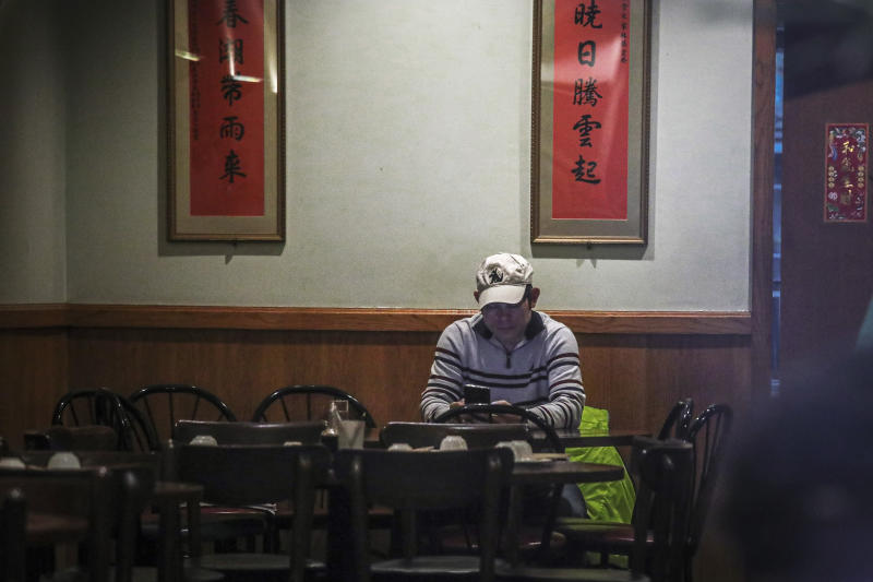 """In this Feb. 13, 2020, photo, Frankie Chu, owner of Vegetarian Dim Sum House in New York's Chinatown, sits in his empty restaurant usually bustling with customers, in New York. Sales have plunged 70% over the last two weeks, """"I don't know how long I can stay here,"""" Chu said. """"After 9/11, it wasn't this bad."""" (AP Photo/Bebeto Matthews)"""