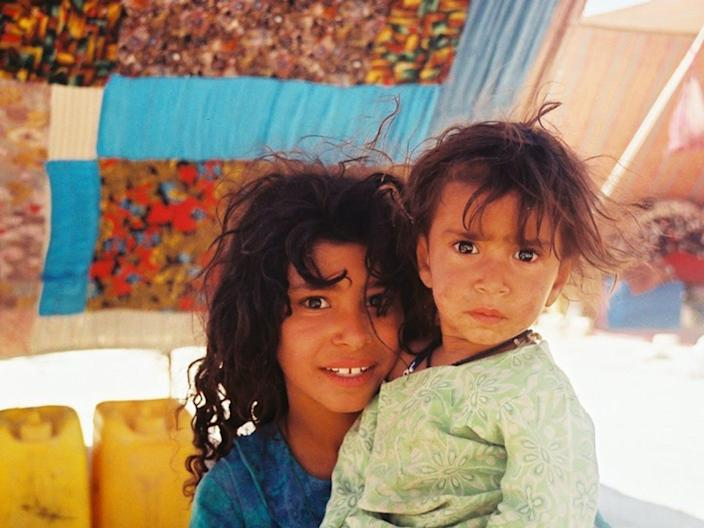 A young girl and her brother sit under a fabric tent