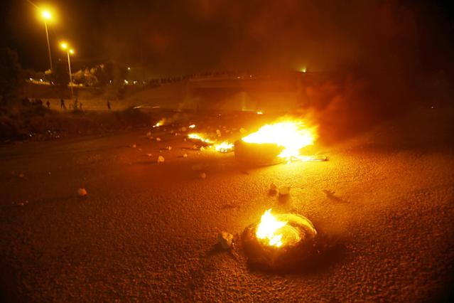 <p>Jordanian youth burn tires and close a highway that links Amman with northern Jordan with rocks as they protest refusing an income tax law in Mastaba village, Jordan, on Friday, June 1, 2018. (Photo: Salah Malkawi/Getty Images) </p>