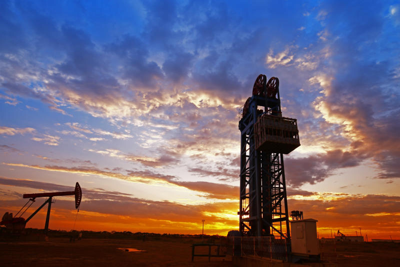 An oil pump and drilling rig at sunset