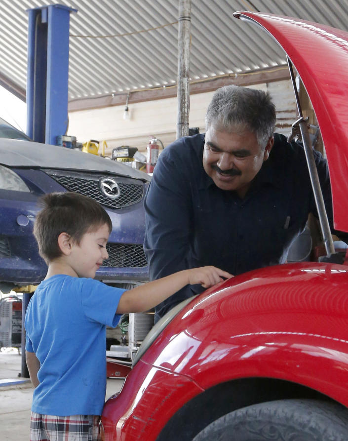 Ruben Moyoroqui, right, talks with his son, Rafael, in his auto repair shop in Tucson, Ariz., on Tuesday, Sept. 4, 2018. Moyoroqui, who came to the U.S. from Mexico in 2001 but overstayed his visa, has four American-born children. When he was pulled over last year, he wasn't cited with any driving infraction but when the office became aware Moroyoqui was in the U.S. illegally, immigration authorities were alerted and he was taken into custody. (AP Photo/Rick Scuteri)