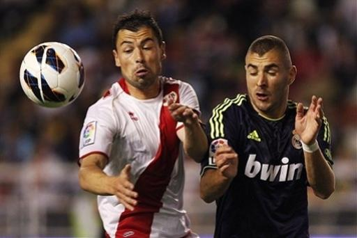 Real Madrid's Karim Benzema from France, right, vies for the ball with Rayo Vallecano's Javi Fuego, during a Spanish La Liga soccer match at the Vallecas stadium in Madrid, Spain, Monday, Sept. 24, 2012. (AP Photo/Andres Kudacki)