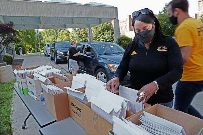 Arcetta Knautz, director of university housing, helps as students move in at the University of Wisconsin-Milwaukee's Sandburg Residence Hall under COVID-19 restrictions.