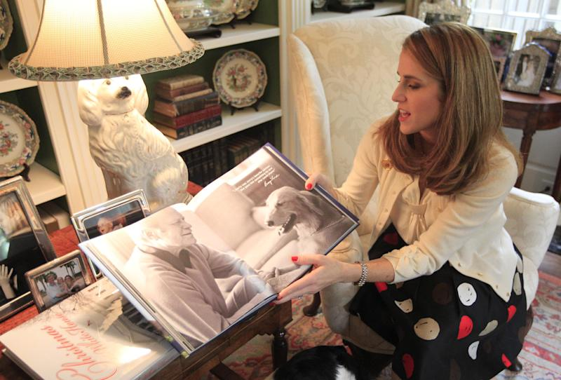 """In this photo made Tuesday, Oct. 16, 2012, Jennifer B. Pickens shows her book titled """"Pets at the White House,"""" during an interview at her home in Dallas. Pickens compiled stories and photos of pets that lived in the White House for her latest book. (AP Photo/LM Otero)"""