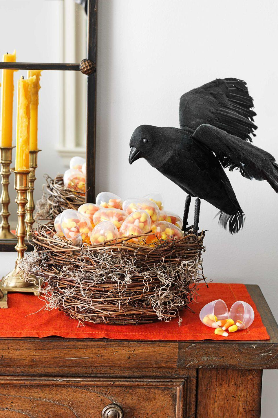 """<p>A crow guards candy corn portioned into <span class=""""redactor-unlink"""">clear plastic eggs</span>. Wrap <span class=""""redactor-unlink"""">grapevine garland</span> around a bowl from the bottom up, using dabs of hot glue to keep it in place. Tuck in a little <span class=""""redactor-unlink"""">Spanish moss</span>; poke the feet of the <span class=""""redactor-unlink"""">crow</span> into the branches to secure it.</p><p><strong>What You'll Need</strong>: <a href=""""https://www.amazon.com/Touch-Black-Feathered-Ravens-Halloween/dp/B07KGD8RTQ/ref=sr_1_5?dchild=1&keywords=fake+raven&qid=1594918771&sr=8-5&tag=syn-yahoo-20&ascsubtag=%5Bartid%7C10070.g.1279%5Bsrc%7Cyahoo-us"""" rel=""""nofollow noopener"""" target=""""_blank"""" data-ylk=""""slk:Fake birds"""" class=""""link rapid-noclick-resp"""">Fake birds</a> ($17, Amazon); <a href=""""https://www.amazon.com/SuperMoss-26911-Spanish-Moss-Natural/dp/B00I6AJ57A/ref=sr_1_1_sspa?dchild=1&keywords=spanish+moss&qid=1595002886&sr=8-1-spons&psc=1&spLa=ZW5jcnlwdGVkUXVhbGlmaWVyPUExTjhOOUROVDg5UTJRJmVuY3J5cHRlZElkPUEwMzQzODYxM0M4WjVaMEE0STlRMyZlbmNyeXB0ZWRBZElkPUEwMTEwMTg0MUQ5MlBaVUVRNTZDSiZ3aWRnZXROYW1lPXNwX2F0ZiZhY3Rpb249Y2xpY2tSZWRpcmVjdCZkb05vdExvZ0NsaWNrPXRydWU%3D&tag=syn-yahoo-20&ascsubtag=%5Bartid%7C10070.g.1279%5Bsrc%7Cyahoo-us"""" rel=""""nofollow noopener"""" target=""""_blank"""" data-ylk=""""slk:Spanish moss"""" class=""""link rapid-noclick-resp"""">Spanish moss</a> ($13, Amazon); <a href=""""https://www.amazon.com/KEIVA-Plastic-Acrylic-Fillable-Ornament/dp/B01NAP8DAX/ref=sr_1_1?dchild=1&keywords=plastic+clear+eggs&qid=1595002930&sr=8-1&tag=syn-yahoo-20&ascsubtag=%5Bartid%7C10070.g.1279%5Bsrc%7Cyahoo-us"""" rel=""""nofollow noopener"""" target=""""_blank"""" data-ylk=""""slk:plastic eggs"""" class=""""link rapid-noclick-resp"""">plastic eggs</a> ($8, Amazon)</p>"""