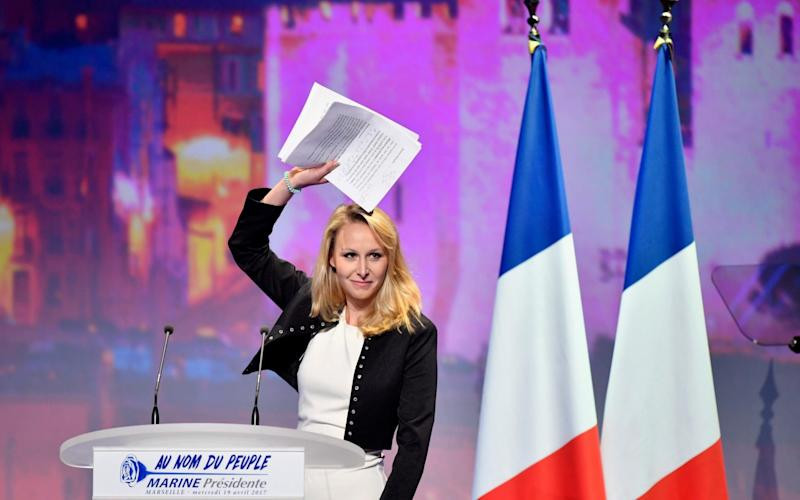 Marion Marechal Le Pen holds a sheaf of papers aloft as she addresses supporters at the rally - Credit: Jeff J Mitchell/Getty Images