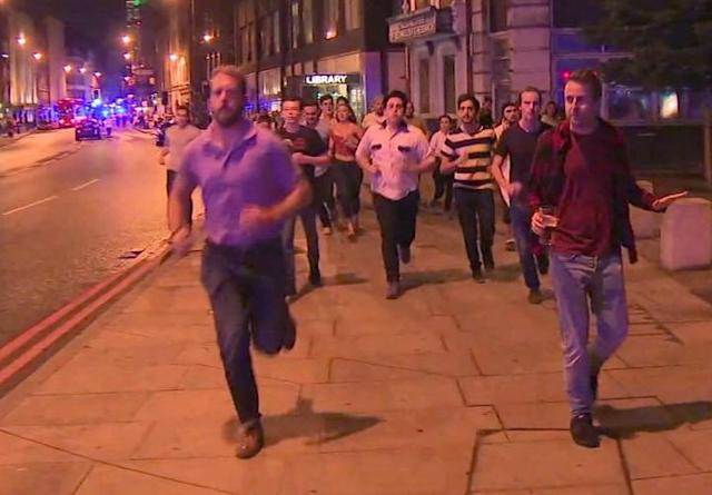 In this image taken from video footage, people run from the scene of attack alongside a man holding a pint of beer, right, in London late Saturday.  (Photo: Sky News via AP)
