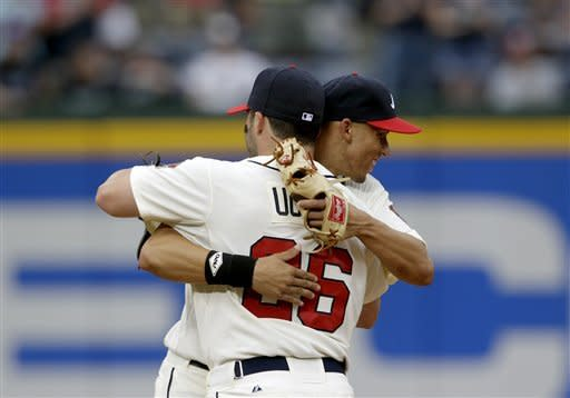 Atlanta Braves' Andrelton Simmons, right, is embraced by teammate Dan Uggla after they defeated the Toronto Blue Jays 5-2 in a baseball game on Saturday, June 9, 2012, in Atlanta. Simmons hit his first major league career home run in the seventh inning. (AP Photo/David Goldman)