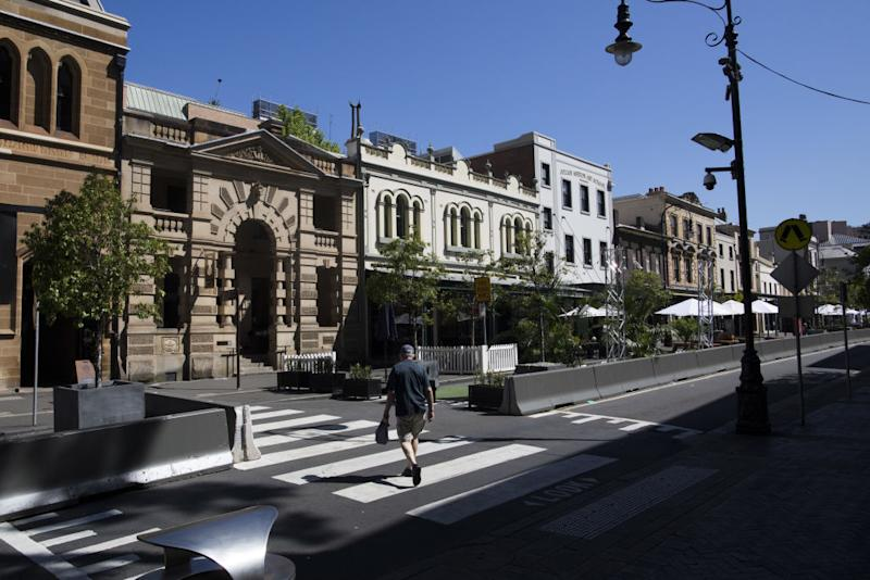 A pedestrian crosses a street in The Rocks area of Sydney, Australia, on Tuesday, Oct. 13, 2020.