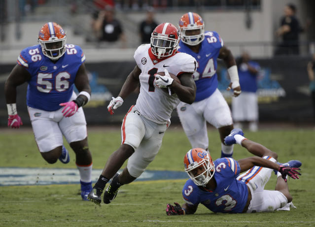 Georgia's Sony Michel (1) runs past Florida defenders including defensive lineman Tedarrell Slaton (56) and cornerback Marco Wilson (3) for a 45-yard touchdown in the second half of an NCAA college football game, Saturday, Oct. 28, 2017, in Jacksonville, Fla. Georgia won 42-7. (AP Photo/John Raoux)