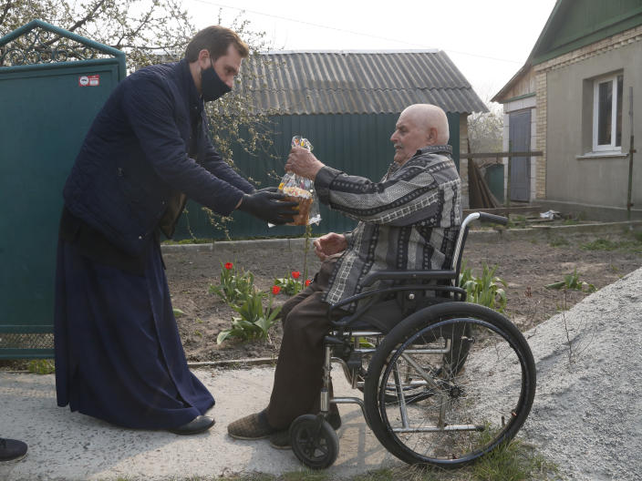 Priest of Ukrainian Orthodox Church Nazariy, wearing a face mask to protect against coronavirus, presents an elderly disabled man with an Easter cake near his house in the village of Nove close to capital Kyiv, Ukraine, Saturday, April, 18, 2020. All the Ukrainian churches have been closed for people because of COVID-19 outbreak, and believers wait for the priest right near their houses. For Orthodox Christians, this is normally a time of reflection, communal mourning and joyful release, of centuries-old ceremonies steeped in symbolism and tradition. But this year, Easter - by far the most significant religious holiday for the world's roughly 300 million Orthodox - has essentially been cancelled. (AP Photo/Efrem Lukatsky)