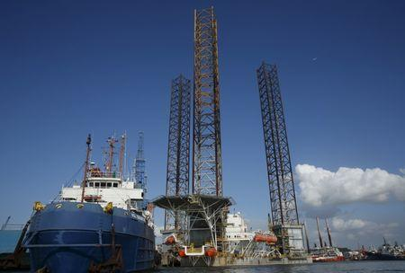 An oil-rig is pictured amongst vessels moored along a row of shipyards northwest of Waterfront City on Batam island, in Indonesia's Riau Islands Province