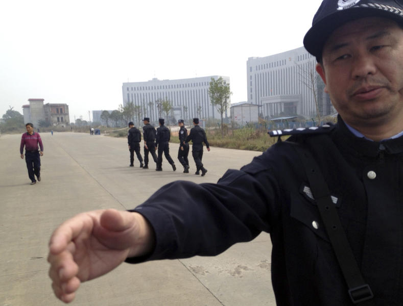A Chinese police officer reaches out towards a journalist outside the courthouse where a trial of Chinese activists is underway in Xinyu city in eastern China's Jiangxi province on Monday, Oct. 28, 2013. Three Chinese activists from a group that urges fellow citizens to embrace their constitutional rights stood trial Monday in the Xinyu district court in a closely watched case that underscores the Communist Party's intolerance of organized political challenge - no matter how small. (AP Photo/Aritz Parra)