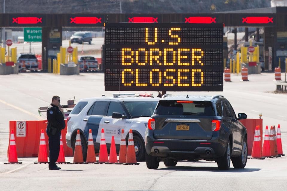 US Customs officers speaks with people in a car beside a sign saying that the US border is closed at the US/Canada border in Lansdowne, Ontario, on March 22, 2020. - The United States agreed with Mexico and Canada to restrict non-essential travel because of the coronavirus, COVID-19, outbreak and is planning to repatriate undocumented immigrants arriving from those countries. (Photo by Lars Hagberg / AFP) (Photo by LARS HAGBERG/AFP via Getty Images)