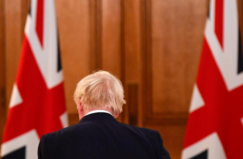 "Britain's Prime Minister Boris Johnson passes Union flags as he leaves following a virtual press conference inside 10 Downing Street in central London on October 12, 2020, after announcing a new COVID-19 alert system. - British Prime Minister Boris Johnson on Monday ordered pubs in Liverpool to shut as part of a new strategy to tackle a surge in coronavirus cases, as staff at three field hospitals across the country were told to prepare for a wave of admissions. The northwest English city is the first to be placed at ""very high risk"" under a new three-tiered system designed to bring order what has become a complex web of local restrictions. (Photo by TOBY MELVILLE / POOL / AFP) (Photo by TOBY MELVILLE/POOL/AFP via Getty Images)"