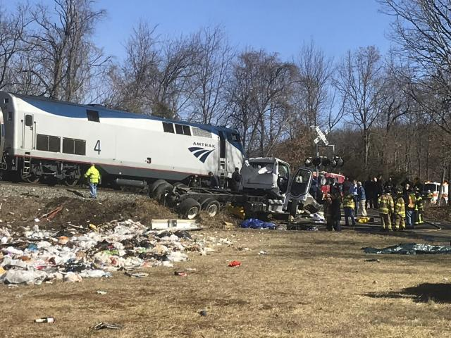 <p>Emergency personnel work at the scene of a train crash involving a garbage truck in Crozet, Va., Jan. 31, 2018. (Photo: Allison Wrabel/The Daily Progress via AP) </p>