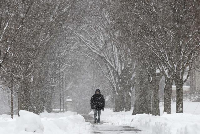 A pedestrian walks through the campus of Phillips Academy during a winter storm in Andover, Mass. Tuesday, March 19, 2013. Winter went out with a blast in the Northeast on Tuesday, snow and sleet closing schools in some areas and making roads an icy, slippery mess a day before spring starts. (AP Photo/Winslow Townson)