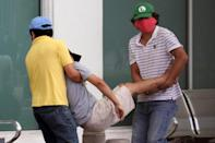 People carry a sick man into a hospital in Guayaquil on April 1 (AFP Photo/Enrique Ortiz)