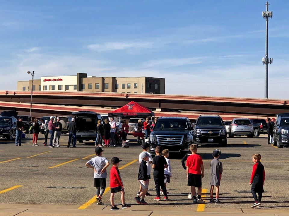 A group of young children stand in a parking lot during the Texas Tech tailgate