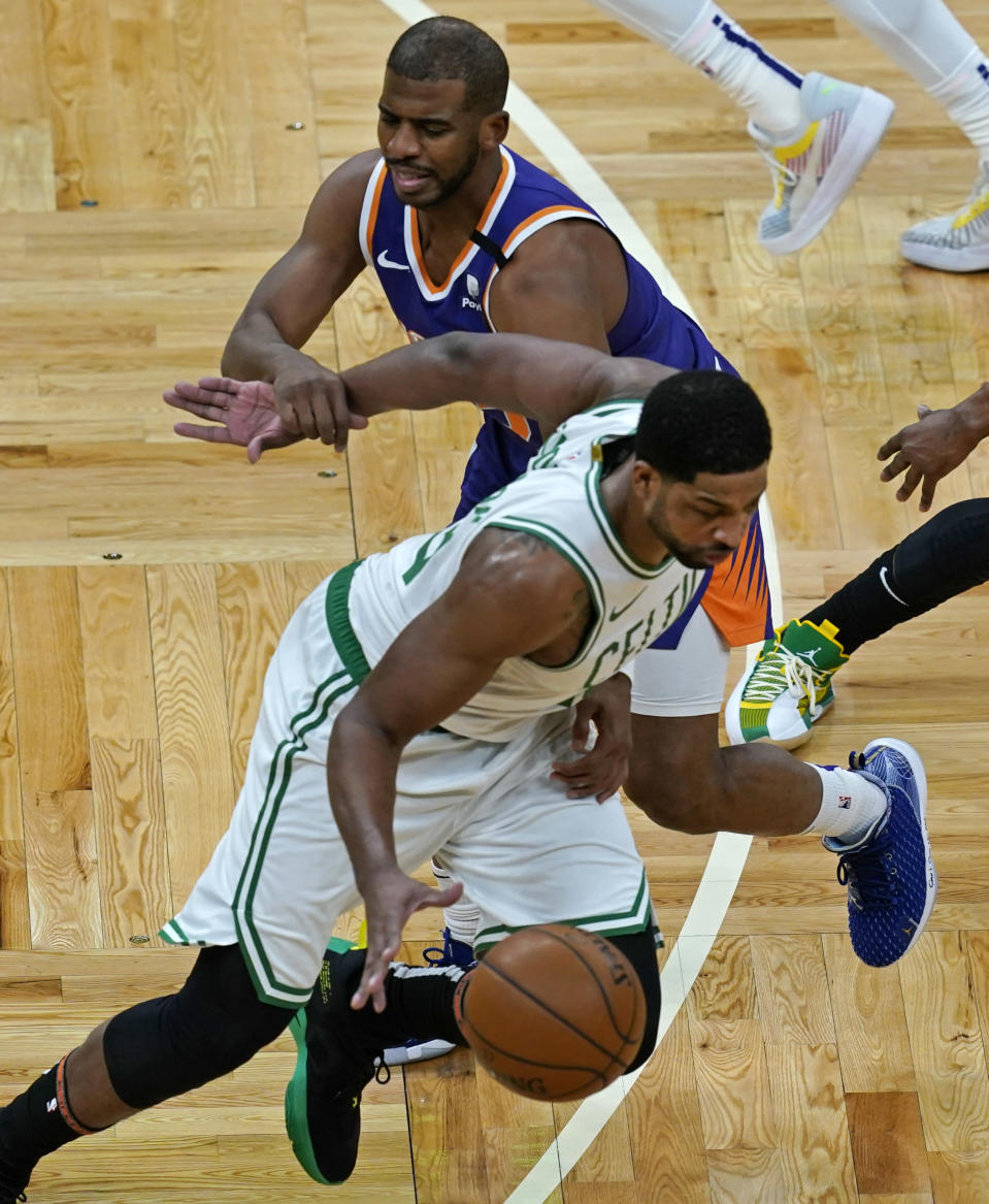 Boston Celtics center Tristan Thompson, below, is fouled by Phoenix Suns guard Chris Paul after he stole the ball from him in the first quarter of an NBA basketball game, Thursday, April 22, 2021, in Boston. (AP Photo/Elise Amendola)