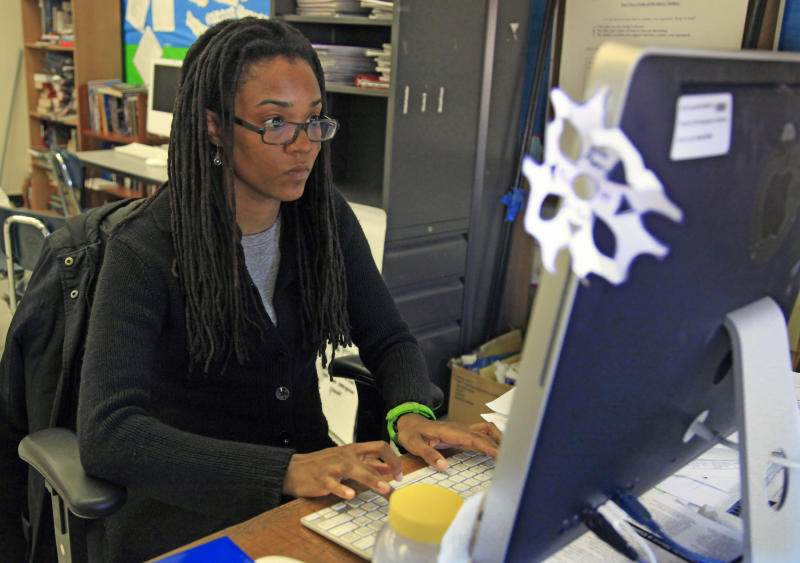 In this April 4, 2012 photo, Nkomo Morris, a teacher at Brooklyn's Art and Media High School, works on her classroom computer in New York. Morris, who teaches English and journalism, said she has about 50 current and former students as Facebook friends. That could be a problem if the new rules instruct teachers not to friend students. (AP Photo/Bebeto Matthews)