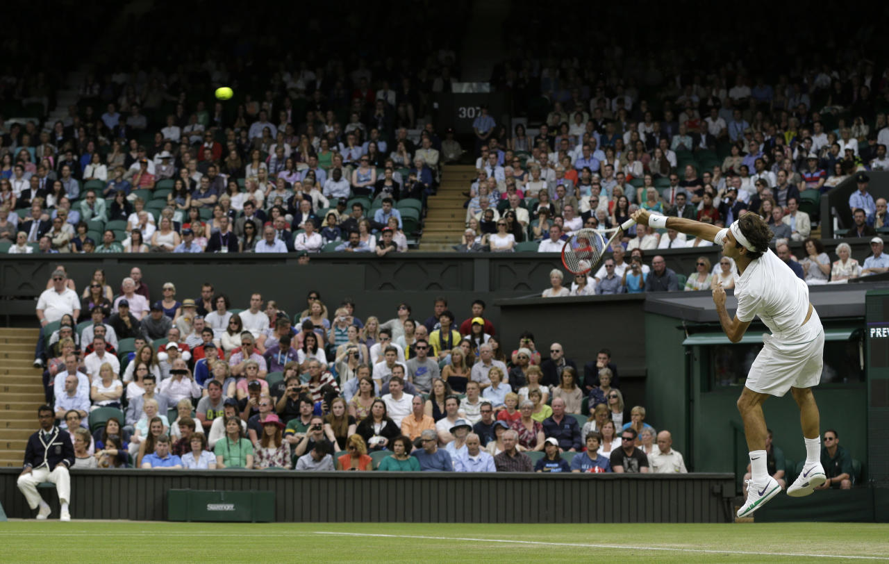 Roger Federer of Switzerland serves to Julien Benneteau of France during a third round men's singles match at the All England Lawn Tennis Championships at Wimbledon, England, Friday, June 29, 2012. (AP Photo/Alastair Grant)