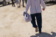 A man carries food from a dining hall at Fort Bliss' Doña Ana Village, in New Mexico, where Afghan refugees are being housed, Friday, Sept. 10, 2021. The Biden administration provided the first public look inside the U.S. military base where Afghans airlifted out of Afghanistan are screened, amid questions about how the government is caring for the refugees and vetting them. (AP Photo/David Goldman)