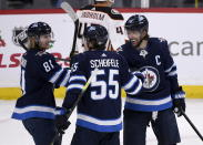 Winnipeg Jets' Mark Scheifele (55) celebrates his game-winning goal against the Anaheim Ducks with Kyle Connor (81) and Blake Wheeler (26) during the third period of an NHL hockey game, Sunday, Dec. 8, 2019 in Winnipeg, Manitoba. (Fred Greenslade/The Canadian Press via AP)
