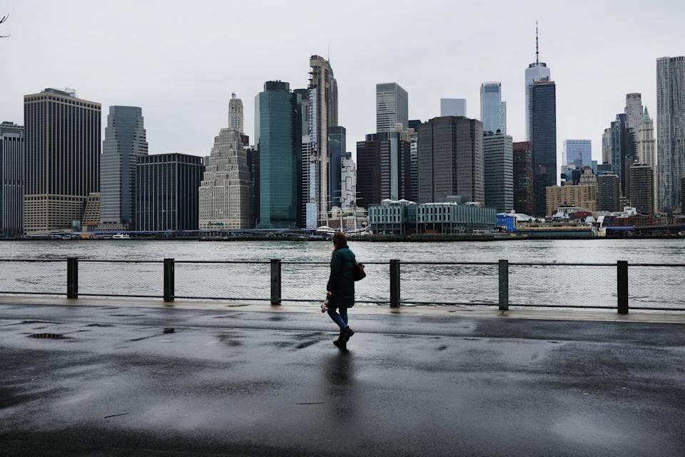 People walk in Brooklyn while lower Manhattan looms in the background, more than 1000 people have died of COVID-19 in the city. Source: Getty Images