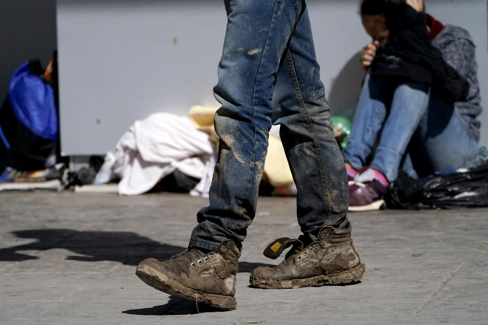 A migrant's muddy shoes are seen without laces as he walks off the customs checkpoint in Reynosa, Mexico, after being deported by U.S. Customs and Border Protection agents, Thursday, March 18, 2021. Migrants are forced to give up their shoelaces as a security measure after being taken into custody. (AP Photo/Julio Cortez)