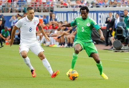 Nigeria defender Efe Ambrose (5) passes the ball as United States forward Clint Dempsey (8) defends during the first half at EverBank Field. Mandatory Credit: Kim Klement-USA TODAY Sports