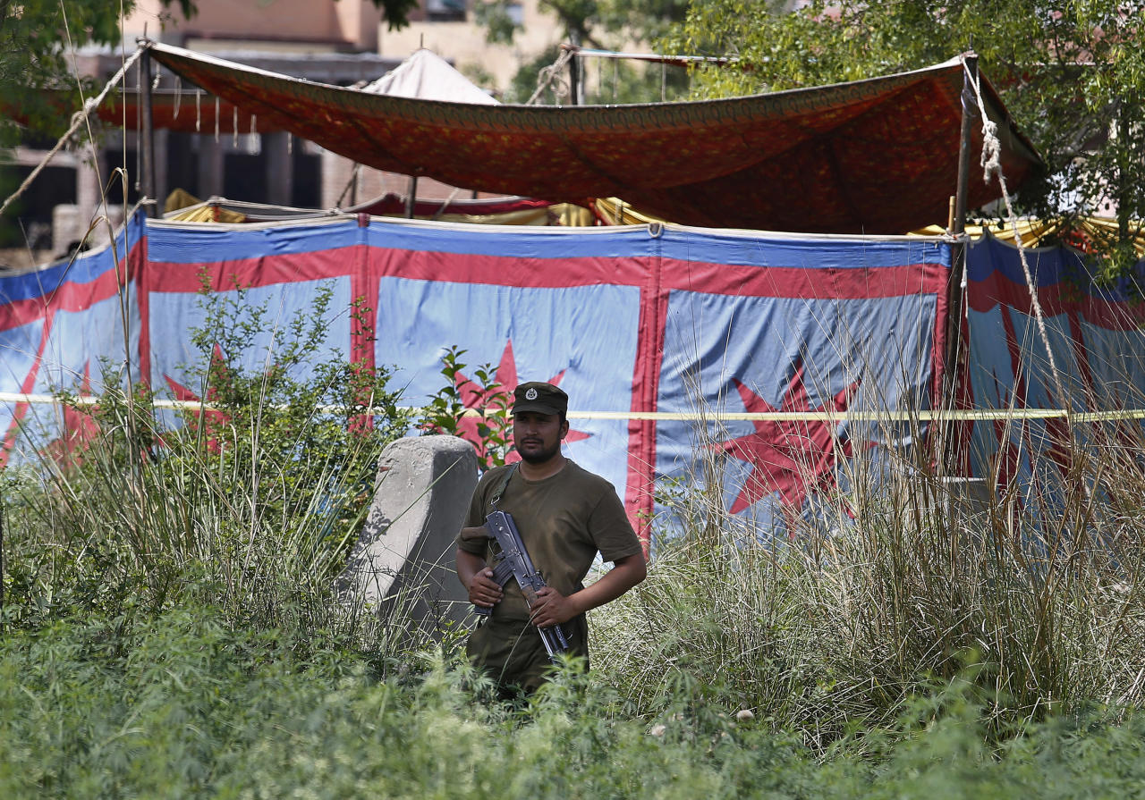 "A Pakistani police officer stands guard near a grave, covered with tent, of Sana Cheema, an Italian woman of Pakistani origin, who was allegedly killed by her family members, in the neighborhood of Mangowal, near Gujrat, Pakistan, Wednesday, April 25, 2018. Pakistani police arrested the father and the uncle suspected in an ""honor"" killing of a 25-year-old Italian citizen, a woman of Pakistani origin who refused to marry the man they chose for her, a police officer said. (AP Photo/Anjum Naveed)"
