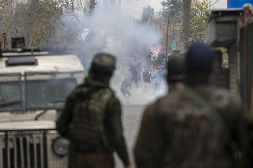 Kashmiri protestors amid tear gas smoke clash with Indian police near the site of a gun battle on the outskirts of Srinagar, Indian controlled Kashmir, Sunday, Nov. 1, 2020. According to police, Indian government forces killed Saifullah Mir, a top rebel commander of the region's largest rebel group, Hizbul Mujahideen which has spearheaded an armed rebellion against Indian rule for decades. (AP Photo/ Dar Yasin)