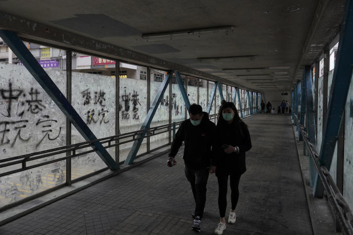 In this Monday, Feb. 10, 2020, photo, a couple wearing protective face masks walks past peeled off posters made by pro-democracy protesters at a footbridge in Hong Kong. The city's often-tumultuous street protests had already slowed in the past two months. Now they have ground to an almost complete halt as attention focuses on how to avoid a recurrence of the SARS pandemic, which killed about 300 people in Hong Kong in 2002-03. (AP Photo/Vincent Yu)