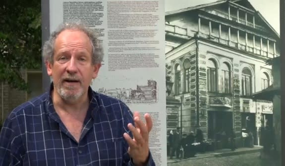 Archaeologist Jon Seligman stands next to a picture of the Great Synagogue of Vilna in Lithuania. Nazi destroyed the synagogue, and now archaeologists are searching for its remains.