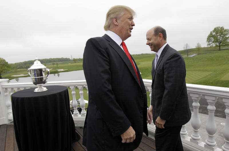 Donald Trump, left, talks to USGA executive director Mike Davis near the U.S. Women's Open trophy during an event Thursday, May 3, 2012, announcing that Trump National in Bedminster, N.J., will host the U.S. Women's Open in 2017. (AP Photo/Julio Cortez)