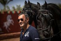 French horse master Joel Proust stands next to horses during a training session with his team in the Moroccan city of Marrakesh