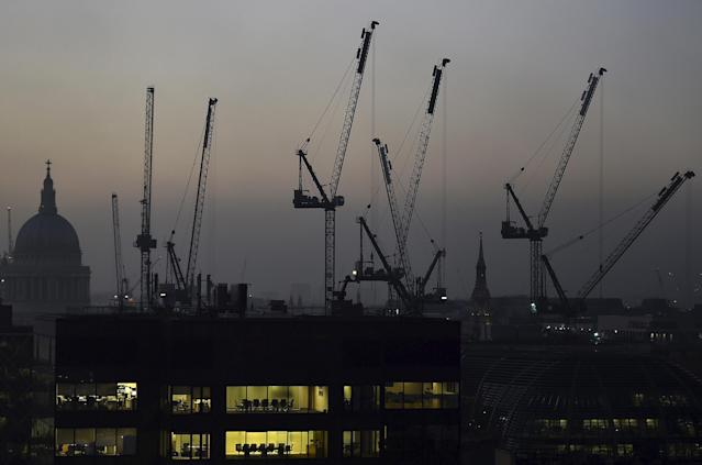 St Paul's Cathedral and building cranes silhouette the City of London skyline at dusk. Photo: Toby Melville/Reuters