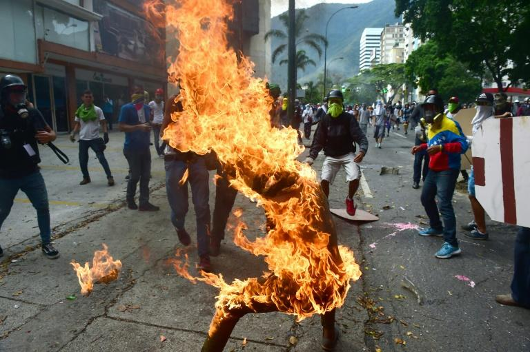 A demonstrator catches fire after the gas tank of a police motorbike exploded during clashes in a protest against Venezuelan President Nicolas Maduro, in Caracas on May 3, 2017