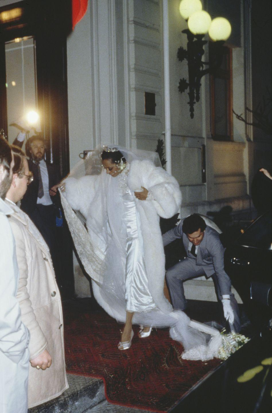 <p>Diana Ross wears a full-length white fur coat to her February nuptials in Romainmotier, Switzerland to Norwegian businessman Arne Naess Jr. The Queen of Motown gets help with her tangled satin and lace dress on her way in.</p>