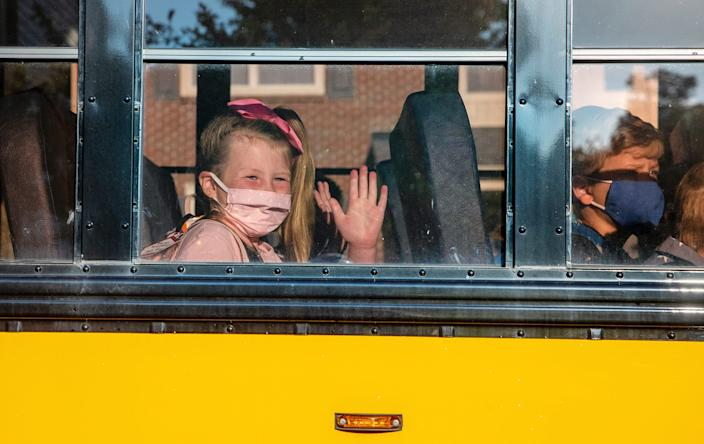 Harper Williams waves from the bus as she prepares for her first day of first grade at Sycamore Elementary School in Avon, Ind., on Wednesday, July 29, 2020.