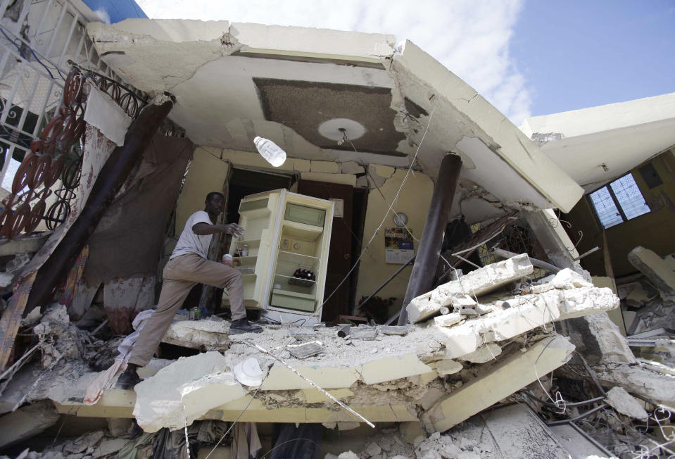 A man empties the refrigerator of his collapsed home in Port-au-Prince, Haiti, on Jan. 14, 2010. (Photo: Julie Jacobson/AP)